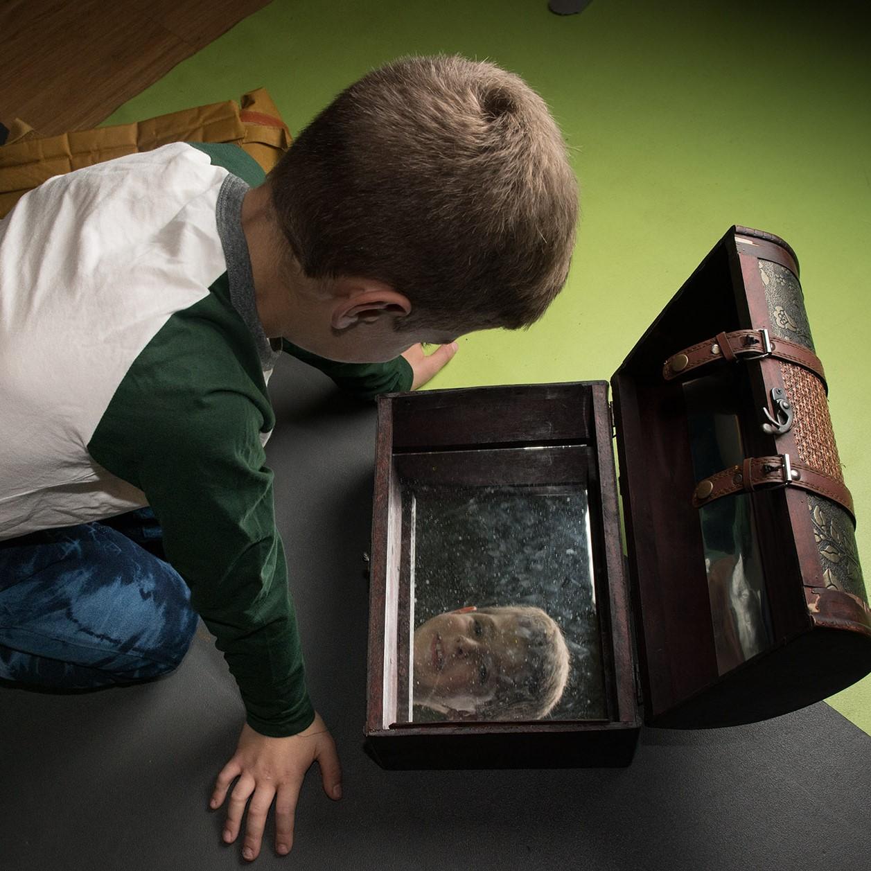 ילד מביט בתיבת האוצר בהצגה מסע בארץ האור